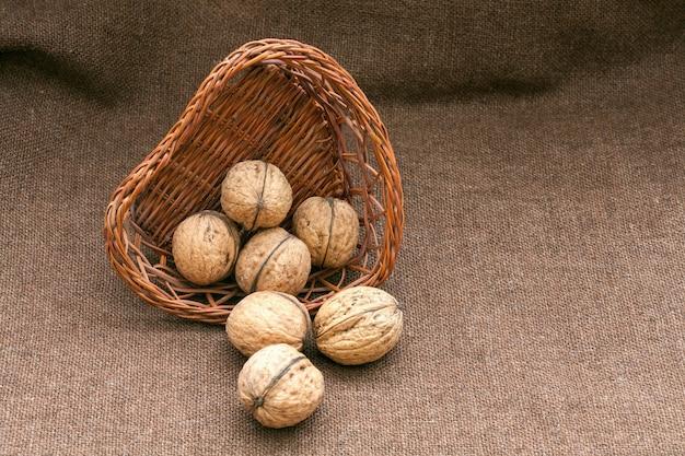 Грецкие орехи в старой плетеной корзине на мешковине