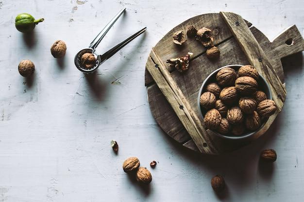 Грецкие орехи в деревянной миске на столе с щелкунчиком.