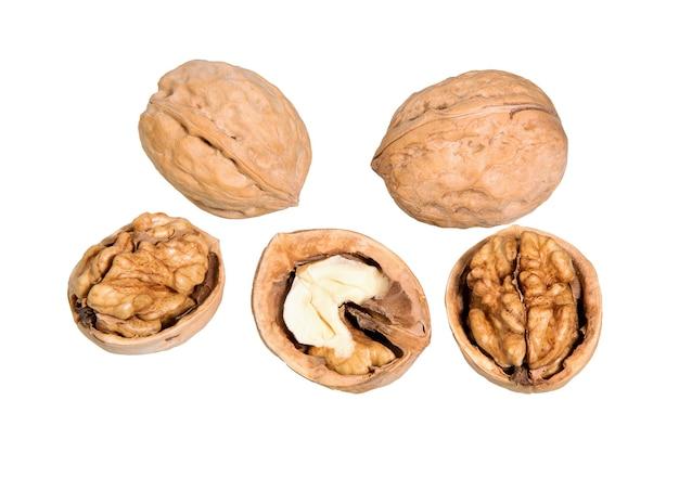 クルミは、白い表面に分離されました。ナッツのマクロ。一般的なクルミのナッツと種子。 Premium写真