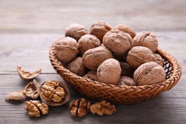 Walnuts kernels in basket on grey wooden background