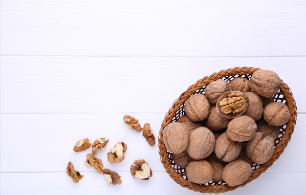 Walnuts kernels in basket on white wooden background