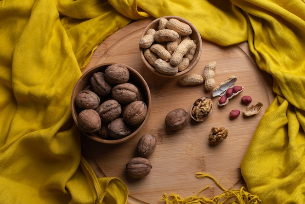 Walnuts kernels on wooden background, nuts in bamboo wooden bowl