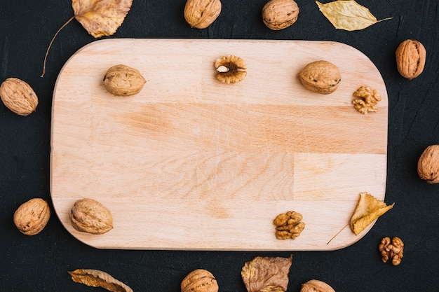 Walnuts and leaves around cutting board