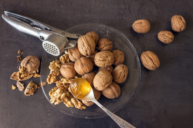 Walnuts lie in a glass dish along with a nutcracker
