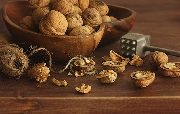 Walnuts lie on a table next to a string rope and a hammer for meat.