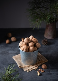 Walnuts in a metal jar on a dark background among fir tree. dark photo
