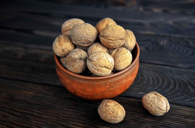 Walnuts, nuts in pottery unpeeled on the table. view from above