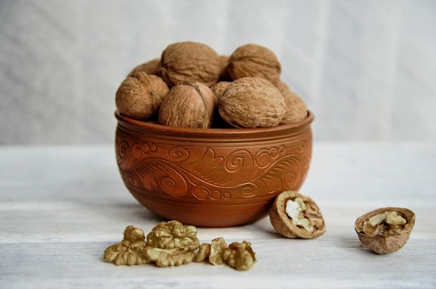 Walnuts, nuts in pottery on a white table. side view