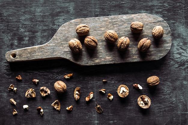 暗いヴィンテージテーブルのクルミ。健康食品。まな板の上にナッツが散らばっています。古いヴィンテージのテーブルとナッツの葉。