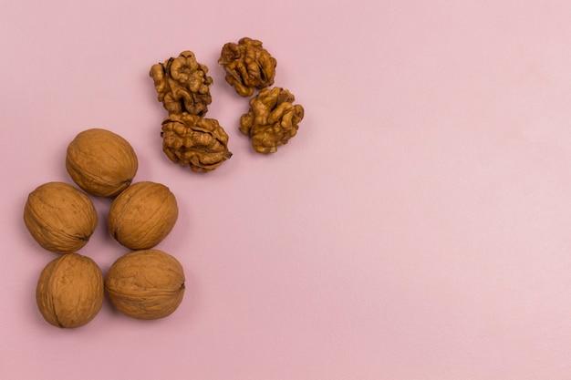 Грецкие орехи на розовом фоне. источник веганского белка и жирных кислот.