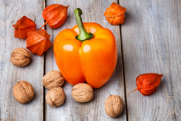 Walnuts, orange pepper and physalis on a wooden background