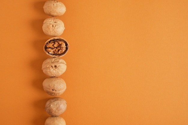 Walnuts pattern on brown background, top view copy space walnuts in shell and without shell in a row