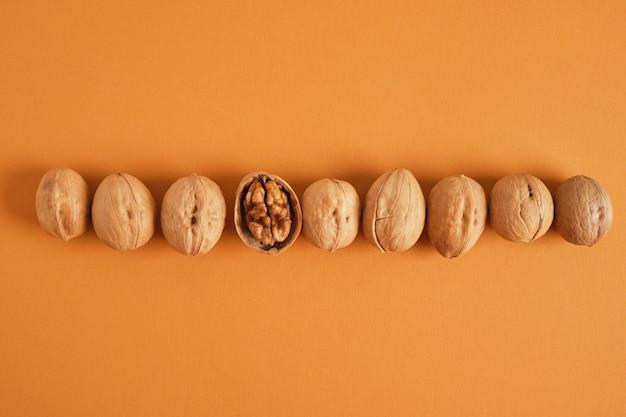 Образец грецких орехов на коричневом фоне, вид сверху копирует космические грецкие орехи в скорлупе и без скорлупы в ряд