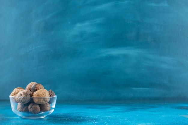 Noci con guscio in una ciotola di vetro, sul tavolo blu.