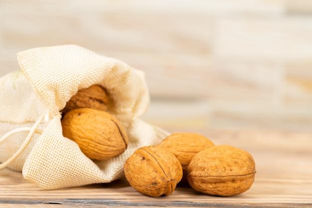 Грецкие орехи высыпались из льняного мешка на столе.