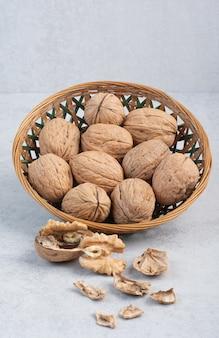 Walnuts and walnut kernels in ceramic bowl