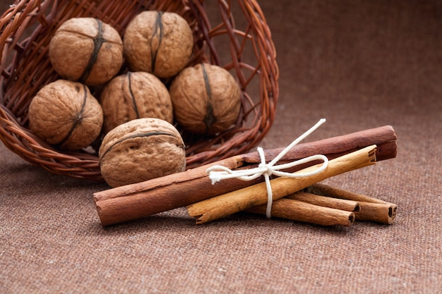 Walnuts in a wicker basket and cinnamon