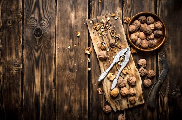 Грецкие орехи с щелкунчиком на доске. на деревянном столе.