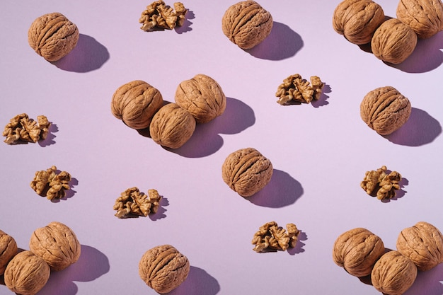 Walnuts with shell and peeled nuts in row composition, minimalist abstract design pattern, healthy food, angle view, purple