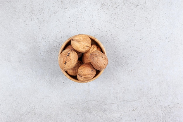 Walnuts in a wooden bowl on marble background.
