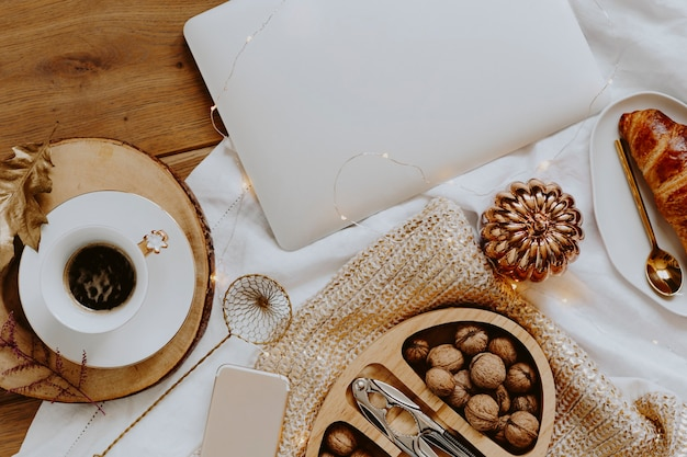 Walnuts in a wooden box served with a cup of coffee next to a laptop