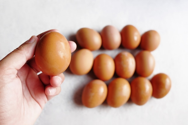 Waman hand holding fresh chicken eggs on white concrete floor background. the benefits of eating eggs are high protein.