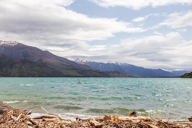 Озеро ванака снег и скалы, камни и вода южный остров новая зеландия