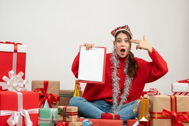 白のプレゼントの周りに座っている彼女の寺院に細かい銃を置くファイルを保持しているサンタの帽子を持つ放浪の少女