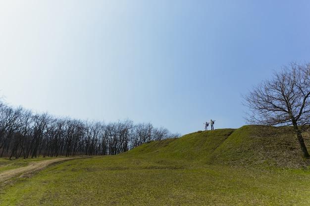 큰 세계의 방랑자. 화창한 날에 나무 근처에 녹색 잔디밭에서 산책하는 관광 복장에 남자와 여자의 세 가족 커플