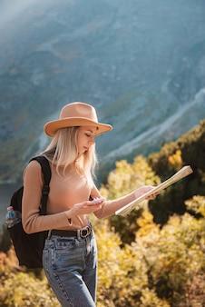 Страсть к путешествиям и концепция путешествий. стильная девушка путешественника в шляпе, глядя на карту, изучает лес. молодой оман с рюкзаком, путешествуя по озеру в лесу.