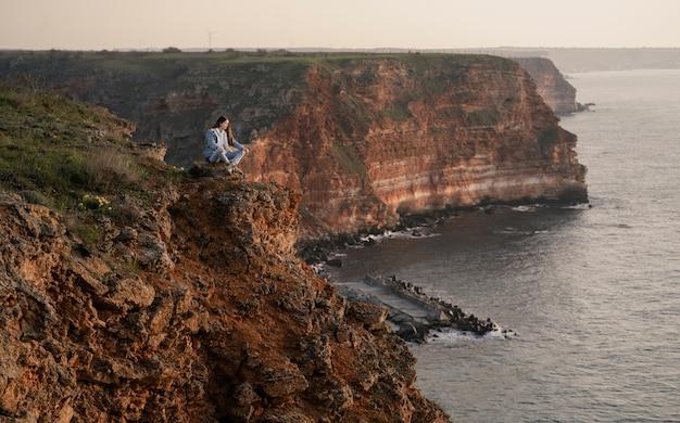 Concetto di voglia di viaggiare con la giovane donna che gode della natura intorno a lei