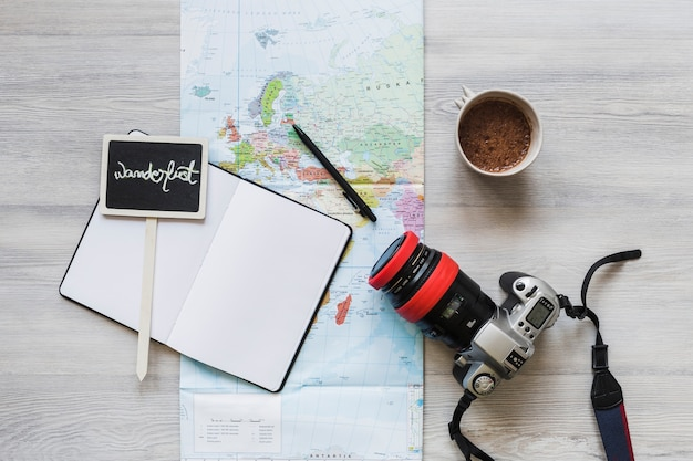 Wanderlust placard over the notebook with map, coffee and camera on desk