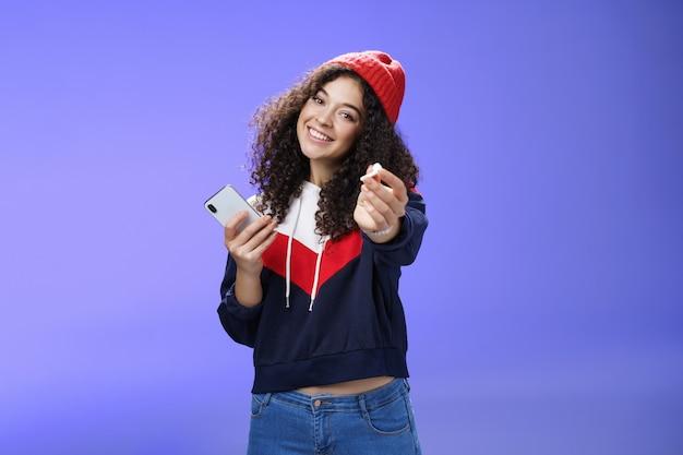 Vuoi ascoltare musica con me ritratto di una donna affascinante e carina con un caldo berretto che si estende sul braccio...
