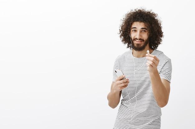 イヤフォンを共有したい。ストライプのtシャツを着たフレンドリーな見栄えの良いスリムな男性モデル。イヤホンをスマートフォンに向けて持ち、