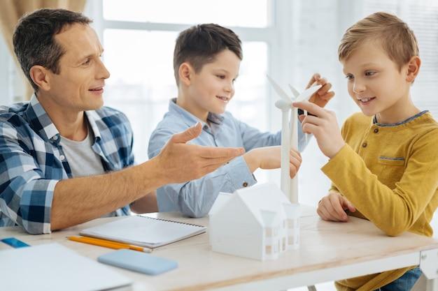 Подражатели инженерам. веселые мальчишки до подросткового возраста разглядывают модели ветряных турбин в офисе отца, пока отец отвечает на их вопросы.