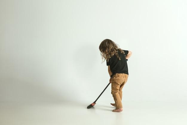 Хочу быть полезным, как папа. маленький ребенок стоит и играет, изолированные на белом пространстве. молодой мальчик со светлыми волосами выглядит игривым и занятым