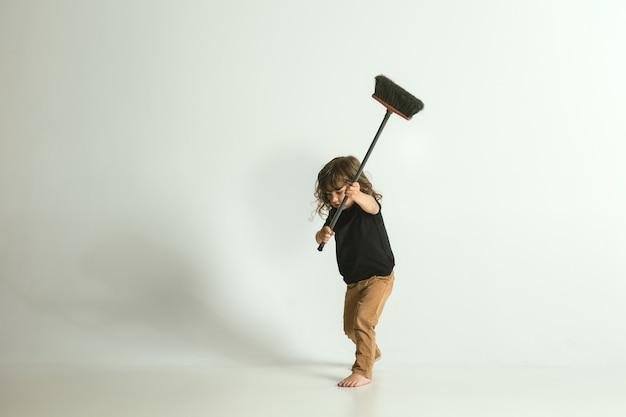 Хочу быть полезным, как папа. маленький ребенок стоит и играет изолированно. молодой мальчик со светлыми волосами выглядит игривым и занятым. понятие детства, счастья, эмоций.