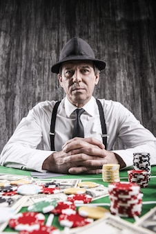 놀고 싶어? 셔츠와 멜빵을 입은 진지한 노인이 포커 테이블에 앉아 주위에 돈과 도박 칩이 든 카드로 카메라를 바라보고 있습니다.