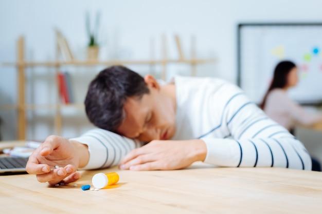 寝たい。非常に気分が悪い間、右手にピルを持ち、腕に頭を置く病気の男性