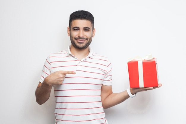 널 원해? 빨간 선물 상자를 들고 손가락으로 가리키는 티셔츠를 입은 쾌활한 젊은 성인 남자의 초상화가 미소로 카메라를 바라보고 있습니다. 실내, 절연, 스튜디오 촬영, 복사 공간, 흰색 배경