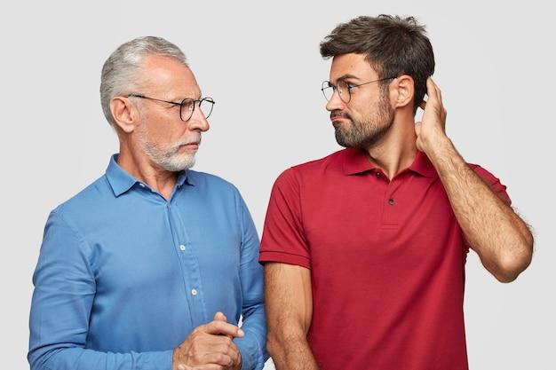 Concetto di guerra delle generazioni. il padre e il figlio maturi e barbuti scontenti si guardano con rabbia, litigano, non riescono a trovare una soluzione comune, posano contro il muro bianco. cattivi rapporti familiari.