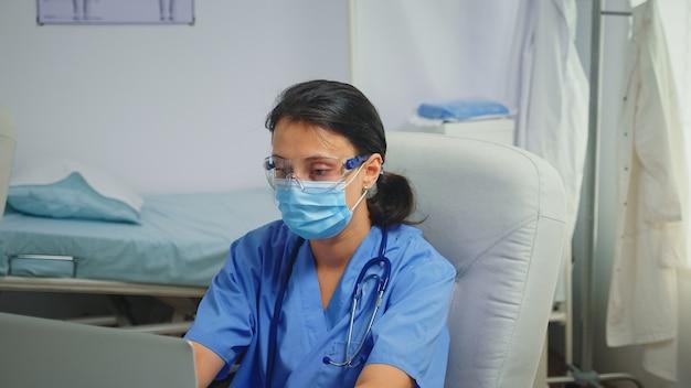 보호 마스크와 안경을 쓴 병동 조수는 노트북에 보고서를 작성합니다. covid-19 동안 병원 캐비닛에서 의료 서비스 상담 치료를 제공하는 의학 전문가