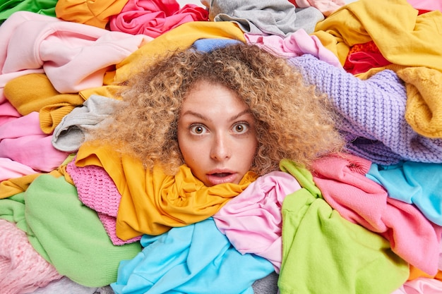 Wardrobe arrangement. womans head sticking through pile of colorful clothes involved in old belongings charity takes part at humanitarian aid organization. female gathers garments for needy people