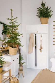 Wardrobe in the decorated bedroom for christmas and new year. christmas trees with lights are in the room in the house