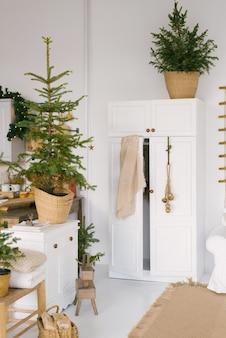 크리스마스와 새해를 위해 꾸며진 침실의 옷장. 조명이 달린 크리스마스 트리가 집안의 방에 있습니다.