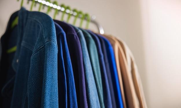 Гардеробная вешалка. мужская одежда висит на баре у белой стены. модный образ жизни стильного мужчины