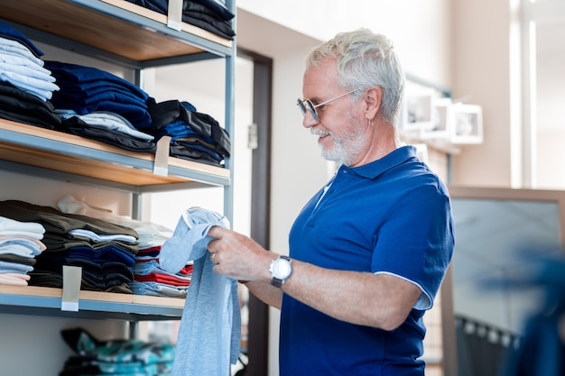 ワードローブのアップデート。その品質を推定しながらtシャツを手に持って驚いた白髪の顧客のプロファイル