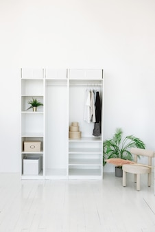 최소한의 스타일 인테리어로 흰색 방에 옷이 달린 옷장
