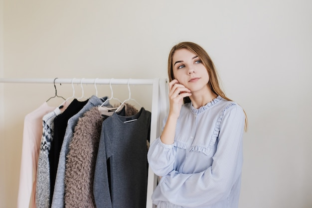 Wardrobe of a young girl. dresses on hangers. flour choice. what to wear? a girl in pajamas does not know what to wear.
