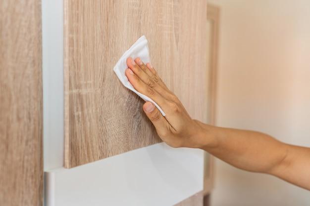 女性の手が自宅の寝室で消毒剤ウェットワイプで木製wardropeをクリーニングします。細菌やウイルスから表面を消毒する概念。閉じる